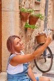Schönheit, die auf alte Stadtpflasterung mit Blumen geht und selfie tut Das Konzept der Reise Stockfoto