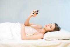 Schönheit, die auf dem Bett mit einer Uhr liegt Lizenzfreie Stockbilder