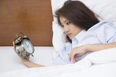 Schönheit, die auf dem Bett schlaflos nachts liegt stockfotografie