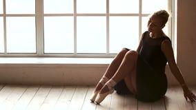 Schönheit, die auf dem Boden in der Ballettklasse sitzt stock video footage