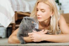 Schönheit, die auf dem Boden mit ihrer Katze liegt Lizenzfreies Stockfoto