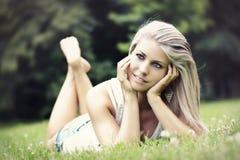 Schönheit, die auf dem Gras liegt Stockfotos