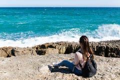 Schönheit, die auf dem Ufer aufpasst die Wellen sitzt lizenzfreies stockfoto