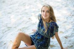 Schönheit, die auf dem weißen Strandsand sitzt Lizenzfreie Stockfotos
