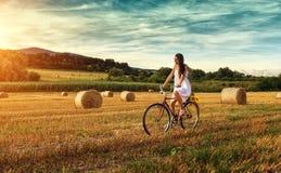 Schönheit, die auf ein altes rotes Fahrrad, auf einem Weizengebiet radfährt Lizenzfreie Stockfotos