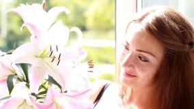 Schönheit, die auf Lilie und Schnüffelngeruch von Blumen schaut stock video