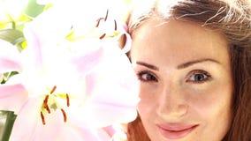 Schönheit, die auf Lilie und Schnüffelngeruch von Blumen schaut stock video footage