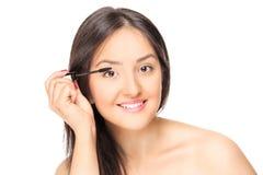 Schönheit, die auf Make-up sich setzt Stockbild
