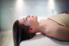 Schönheit, die auf Massagebett sich entspannt lizenzfreie stockbilder