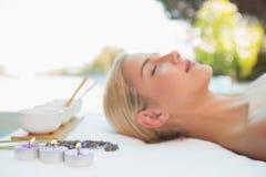Schönheit, die auf Massagetabelle in der Badekurortmitte liegt Lizenzfreie Stockfotos