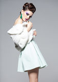 Schönheit, die blaues Make-up und weißen den Pelz aufwirft im Studio trägt Lizenzfreies Stockfoto
