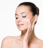 Schönheit, die Creme auf Gesicht aufträgt lizenzfreies stockbild