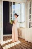 Schönheit, die das lange Kleid hält Zimmerpflanze trägt stockfoto