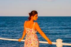 Schönheit, die den Sonnenuntergang, stehend auf dem Strand aufpasst Lizenzfreie Stockfotografie