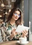Schönheit, die ebook Leser in einem Café verwendet stockbild