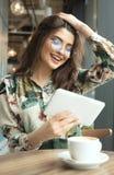 Schönheit, die ebook Leser in einem Café verwendet stockfotografie