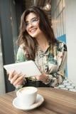 Schönheit, die ebook Leser in einem Café verwendet lizenzfreie stockfotografie