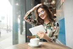 Schönheit, die ebook Leser in einem Café verwendet lizenzfreie stockbilder