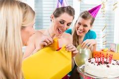 Schönheit, die eine Geschenkbox beim Feiern ihres birthda öffnet stockbild