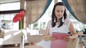 Schönheit, die eine Tablette in einer Hotellobby sitzt verwendet, einen Tasse Kaffee genießend auf einer aufwändigen lächelnden C stock video