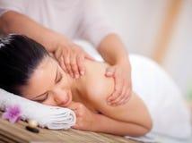 Schönheit, die eine Wellnessrückenmassage am Badekurortsalon hat Lizenzfreies Stockfoto