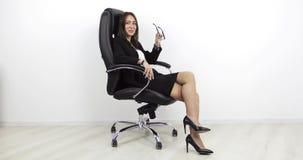 Schönheit, die in einem schwarzen ledernen Bürostuhl sitzt und Gläser entfernt stock video