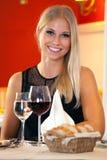 Schönheit, die an einem Tisch in einem Restaurant sitzt Lizenzfreie Stockfotos