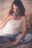 Schönheit, die einen Kaffee in ihrem Bett trinkt Enthalten Sie Steigungs- und Ausschnittsmaske Stockfotografie