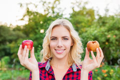 Schönheit, die faulen und guten Apfel hält Stockfotografie