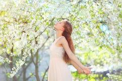 Schönheit, die Geruch in blühendem Frühlingsgarten genießt lizenzfreie stockfotos