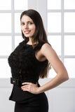 Schönheit, die hinten in einem schwarzen Kleid über Studiodachbodenausgangsinnentüren steht Lizenzfreies Stockbild