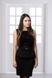 Schönheit, die hinten in einem schwarzen Kleid über Studiodachbodenausgangsinnentüren steht Lizenzfreie Stockfotos