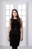 Schönheit, die hinten in einem schwarzen Kleid über Studiodachbodenausgangsinnentüren steht Lizenzfreie Stockfotografie