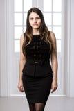 Schönheit, die hinten in einem schwarzen Kleid über Studiodachbodenausgangsinnentüren steht Lizenzfreies Stockfoto
