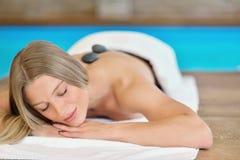 Schönheit, die im Badekurortsalon mit heißen Steinen auf Körper sich entspannt Schönheitsbehandlungstherapie stockbild