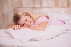 Schönheit, die im Bett aufwacht Lizenzfreies Stockfoto
