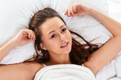 Schönheit, die im Bettporträt lächelt Lizenzfreie Stockfotografie
