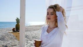 Schönheit, die im Bungalow mit weißen Vorhängen auf Ufer, Mädchen stillsteht auf Strand sitzt, trinkender Kokosnusssaft, stock video