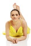 Schönheit, die im gelben Kleid liegt Stockfotografie