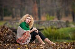 Schönheit, die im Park während der Herbstsaison aufwirft. Blondes Mädchen, das grüne Bluse und große die Schalaufstellung im Freie Stockbilder