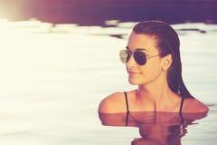 Schönheit, die im Pool bei Sonnenuntergang sich entspannt Lizenzfreie Stockfotos