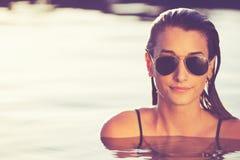 Schönheit, die im Pool bei Sonnenuntergang sich entspannt Stockfotos