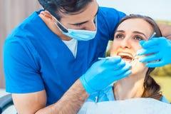 Schönheit, die im Vertrauen ihrem zuverlässigen Zahnarzt betrachtet Stockfoto