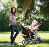Schönheit, die Kinderwagen im Park drückt Lizenzfreies Stockbild