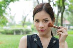 Schönheit, die Kosmetik mit Make-upbürste auf Gesicht aufträgt lizenzfreies stockfoto