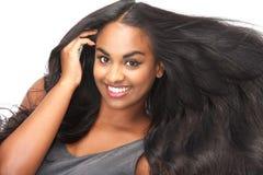 Schönheit, die mit dem flüssigen Haar lokalisiert auf Weiß lächelt