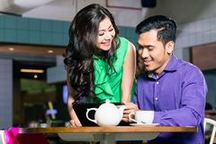 Schönheit, die mit Liebe ihrem Freund in einer Kaffeestube betrachtet stockfotografie