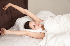 Schönheit, die mit Vergnügen am Bett ausdehnt lizenzfreies stockbild