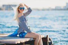 Schönheit, die nahe dem Meer sitzt Stockfoto