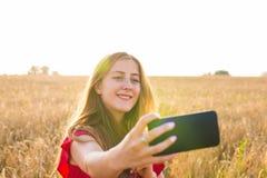 Schönheit, die selfie Foto von auf dem gelben Gebiet mit Naturhintergrund macht Schließen Sie herauf Porträt Junge lizenzfreie stockfotos